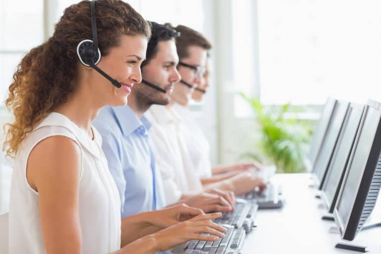 Smiling people working in a successful call center